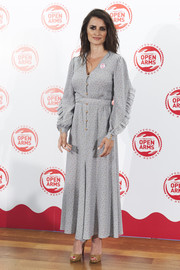 Penelope Cruz went for a demure gray print dress with ruffled sleeves at the Open Arms benefit dinner.