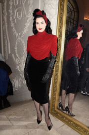 Dita Von Teese layered a draped red turtleneck top over a velvet LBD for the Jean Paul Gaultier Couture show.