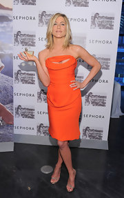 Jennifer Aniston teamed her orange cutout dress with nude patent Anna sandals.