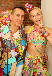 Miley Cyrus went all out with the colors for the Jeremy Scott fashion show, teaming layers of bangles with a mixed-print outfit and some beaded necklaces.