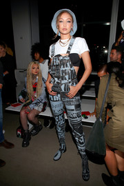 Gigi Hadid kept it youthful in printed overalls by Jeremy Scott during the brand's fashion show.