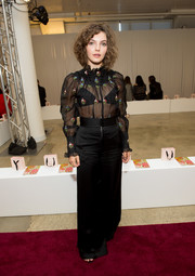 Camren Bicondova paired her blouse with black wide-leg pants.