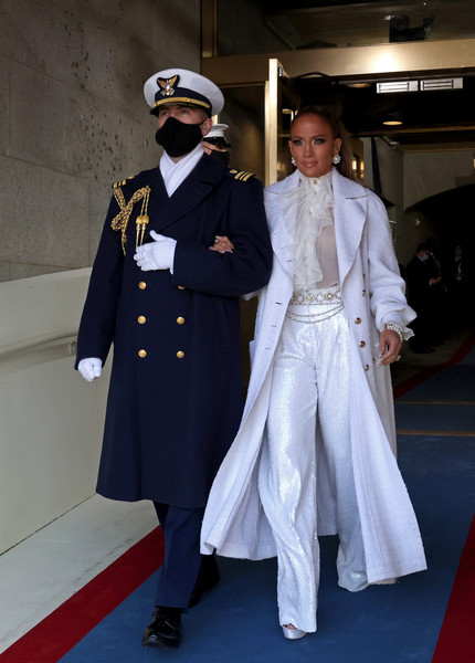 Jennifer Lopez teamed sequined, wide-leg pants with a ruffle blouse and a tweed coat, all by Chanel, for Joe Biden's inauguration.