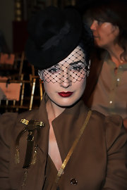 Dita completed her tan trench coat with a black fedora hat.