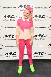JoJo Siwa punctuated her pink outfit with neon-green sneakers.