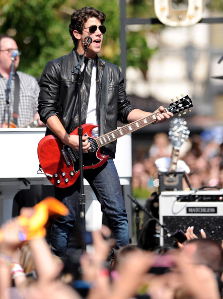 Nick hit the stage with his brothers wearing a black leather jacket with jeans and classic aviator shades.