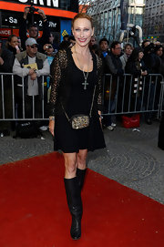 Andrea strikes a pose in black leather knee-high boots. She pairs the boots with a slightly a-line black dress.