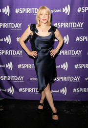 Courtney Love chose a slinky black satin dress with ruffled shoulder straps and an asymmetrical hem for the 'Believer' Spirit Day concert.