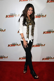 Selena Gomez rocked a pair of intricately cutout boots with a pair of skinny jeans and on trend leopard print scarf.