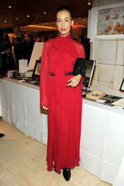 Maggie Q looked modest yet stylish in a long-sleeve red tie-neck dress when she attended the Believe Gala.