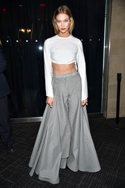 Karlie Kloss put her toned abs on display in a white Rosie Assoulin crop-top while attending the Kanye West Yeezy Season 3 fashion show.