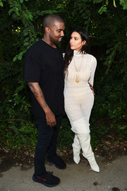 Kim Kardashian donned a sheer white turtleneck dress by Yeezy, revealing a high-cut bodysuit underneath, for the Yeezy season 4 fashion show.