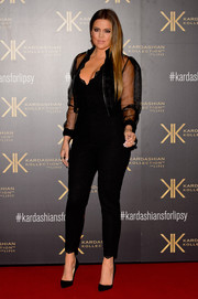 Khloe Kardashian went for a seductive look with a tight black jumpsuit and a matching sheer jacket during the Kardashian Kollection for Lipsy launch.