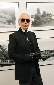 Karl keeps his signature poise in a black suit with white accents. He finishes his signature look with black avaitor sunglasses. They are a great contrast with his white blonde hair.