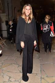 Olivia Palermo attended the Kenzo fashion show wearing black flare jeans and a slouchy blouse.