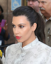 Kim Kardashian kept her look cool and professional with a cherry red lip.