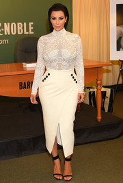 Kim Kardashian flaunted her hourglass figure in a tight white Christian Dior turtleneck during her book signing.