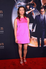 Sophie Cookson's strappy red peep-toes provided a striking contrast to her pink dress.