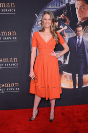 Julie Henderson cut a shapely silhouette in an orange fit-and-flare dress, featuring a plunging V neckline and mesh piping, during the 'Kingsman: The Secret Service' premiere.