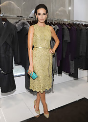 Camilla Belle wore this gold lace dress with a metallic belt to the Kors Collaborations party.