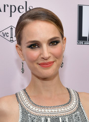 Natalie Portman contrasted her dark eye makeup with bright coral lipstick.