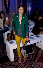 The master of making the unexpected work with ease, Olivia Palermo hit the Anya Hindmarch show in an emerald green blazer and vibrant yellow pants.