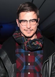 Josh looks ready to cozy up by a fireplace in his plaid shirt and contrasting plaid scarf.