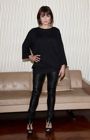 Valentina wears a loose knit top over black leggings for this chic look.