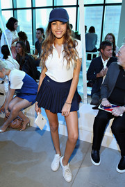 Madison Beer accessorized with a simple white leather wristlet by Lacoste.
