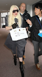 Lady Gaga showcased her eccentric style at the Japan airport in patent leather lace up boots.