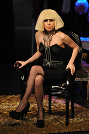 Lady Gaga is wearing a fashion forward edgy cut. It is a volumized straight cut with her gothic styled black strapless cone dress.
