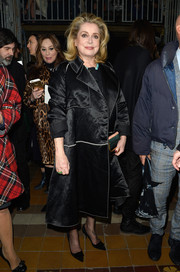 Catherine Deneuve attended the Lanvin fashion show looking regal in a black satin coat.