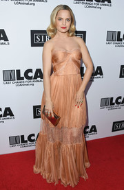 Mena Suvari polished off her look with a gold box clutch.