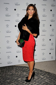 Eva does old hollywood glamour to a T in this black fur stole and red brocade dress.