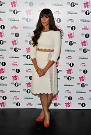 Leona Lewis accented her white scalloped two piece ensemble with coral suede pumps.