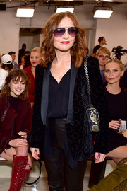 Isabelle Huppert attended the Longchamp Spring 2019 show wearing a navy velvet blazer from the label.