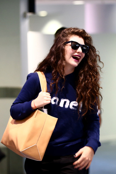 Lorde paired her outfit with an orange leather bag.