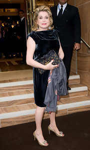 Catherine Deneuve paired her cocktail dress with a printed clutch.