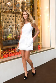 Elle showed off her famous mile-long legs with a bright white mini dress and ruffle-embellished, peep toe slingbacks.