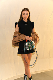 Emma Chamberlain looked darling in a little black dress with a ruffle neckline and shoulders at the Louis Vuitton Cruise 2020 show.