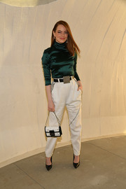 Emma Stone looked effortlessly stylish in an emerald satin turtleneck at the Louis Vuitton Cruise 2020 show.