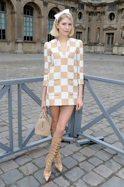 Elena Perminova's knee-high gladiator heels add some edge to her feminine look at Paris Fashion Week.