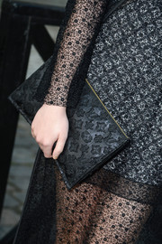 Dakota Fanning attended the Louis Vuitton fashion show carrying this ultra-chic monogram clutch.