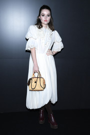 Kaitlyn Dever went boho in a white Louis Vuitton midi dress with ruffle detailing, puffed sleeves, and a bubble hem during the brand's Fall 2020 show.