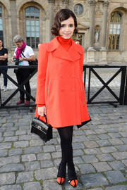 Miroslava Duma went for a retro vibe with an orange swing coat, dark tights, and mod platform pumps at the Louis Vuitton fashion show.