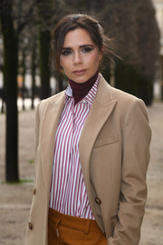 Victoria Beckham teamed a striped shirt with a burgundy turtleneck and a beige coat for the Louis Vuitton Menswear show.