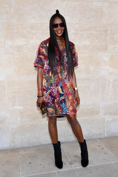Naomi Campbell teamed her vibrant dress with black velvet ankle boots.