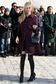 Nicola Peltz was all about retro elegance in a plum-colored cape coat at the Louis Vuitton fashion show.