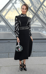 Alicia Vikander looked ladylike in a black Louis Vuitton midi dress with a floral neckline and sleeves during the brand's Fall 2019 show.