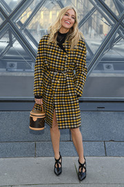 Sienna Miller bundled up in a checkered coat by Louis Vuitton for the brand's Fall 2019 show.